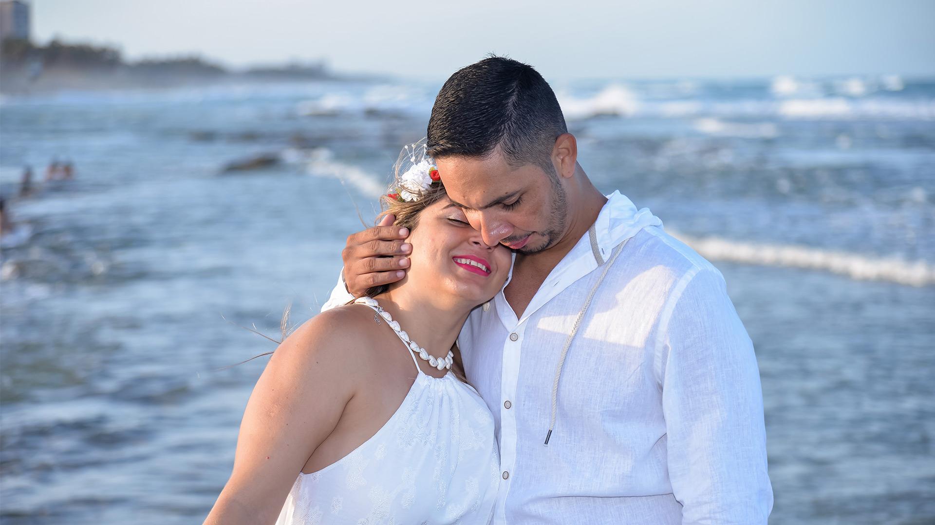 Casal de noivos abraçados na praia