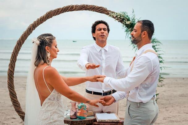 Celebrante realizando a benção das alianças em casamento na praia