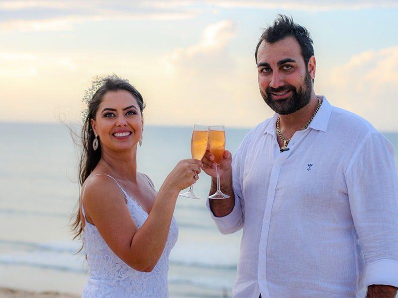 Casal de noivos brindando com taça de champanhe seu casamento em Jericoacoara