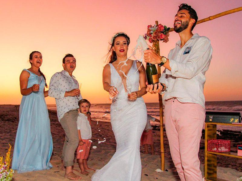 Noivo estourando champanhe comemorando casamento junto com a noiva e convidados na praia